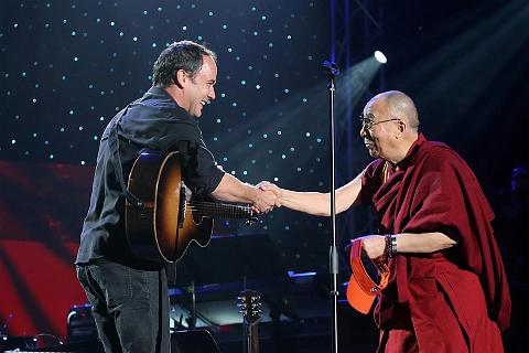 Dave Matthews and His Holiness the Dalai Lama shake hands onstage at the One World Concert at Syracuse University on October 9, 2012 in Syracuse, New York, USA