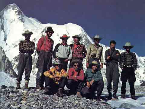 The expedition poses in front of Gasherbrum I (Hidden Peak) at Base Camp after the first ascent in 1958. Behind the team is Gasherbrum I (Hidden Peak) above the Abrruzzi Glacier. The summit on the left, Hidden South in the middle, and the Roch ridge used by the expedition on the far right. Front, left to right: Bob Swift, Tom Nevison, Dick Irvin. Rear: Mohd Akram, Gil Roberts, Ras Rizvi, Pete Schoening, Nick Clinch, Andy Kauffman, Tom McCormack. - A Walk In The Sky book - A Walk In The Sky book