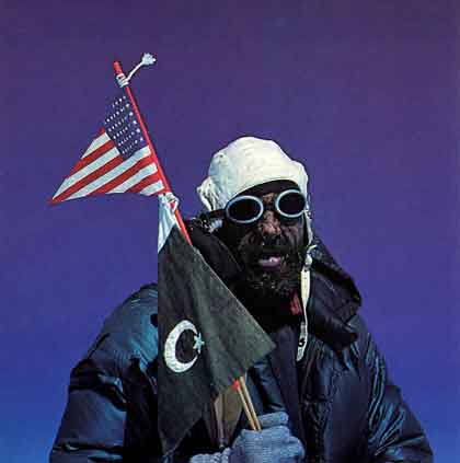 Andy Kauffman holds the American flag and the Pakistani flag on the summit of Gasherbrum I (Hidden Peak) after the first ascent on July 5, 1958 - A Walk In The Sky book