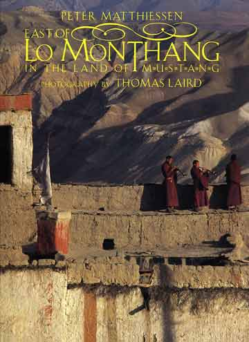 Monks on the walls of Lo Manthang blow horns to announce the end of the Tiji Festival - East of Lo Monthang book cover