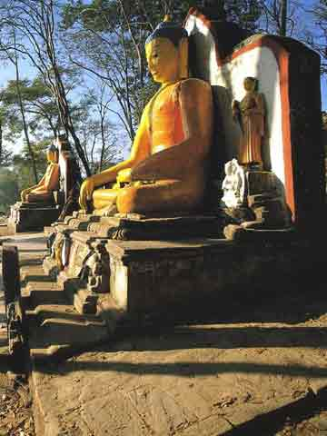 Stone Buddhas flank the stairs at the foot of the steps to Swayambhunath - Nepal: The Mountains Of Heaven book