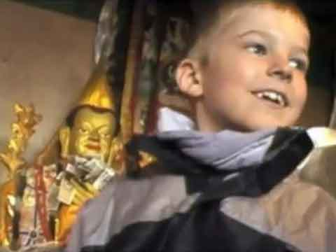 Young son inside monastery with Buddhist statues - Tibet An Adventure With Our Children Youtube Video by Ed van der Kooy and Piet Warffemius
