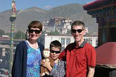 Charlotte Ryan, Dangles, Peter Ryan, and Jerome Ryan pose on the roof of the Jokhang Temple with the Potala Palace behind.