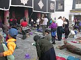 We watched the devout pilgrims prostrate themselves at the Jokhang Temple's entrance doors. Their hands are protected by large mittens or small block of wood fixed to the waist by a lace. People kneel, their hands reach the ground and they start sliding until the whole body extends on the ground too. Standing up they then repeat the action again and again.